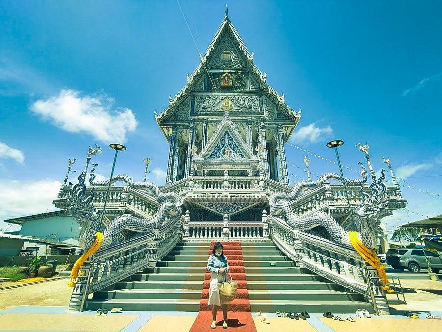 A woman standing in front of beautiful Wat Pak Nam Khaem Nu Temple in Chanthaburi.